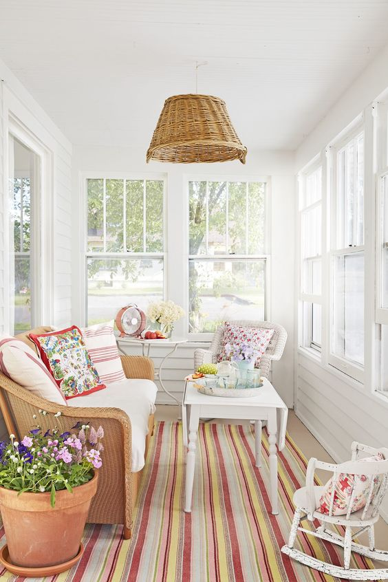a small yet vibrant sunroom with neutral furniture, colorful printed textiles, a wicker pendant lamp and potted flowers