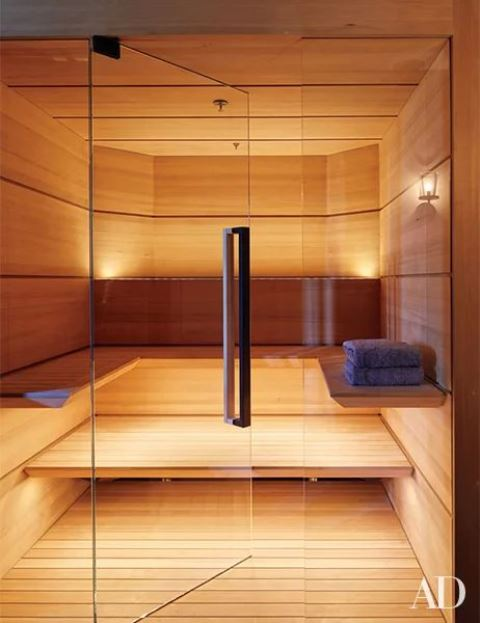 a small yet welcoming wood clad steam room with a couple of benches along the wall and built-in lights
