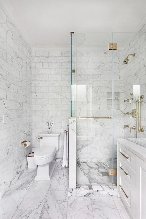 a sophisticated wihte marble tile bathroom with a shower space with a half wall, a white vanity and gold touches for more elegance