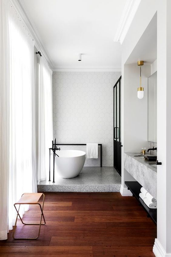 a stone platform under the bathtub is a cool idea to highlight this bathing oasis and give an edge to the bathroom