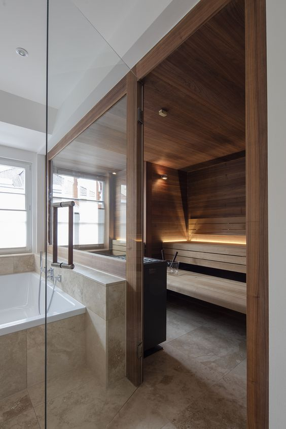 a stylish modern sauna with a glass wall, wood all over it and some intimate light for an ambience