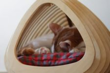 a stylish plywood fish-shaped cat bed with a cushion is a cool unit for a modern space