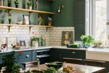 a stylish vintage kitchen with green walls, white subway tiles, teal cabinets, a dark stained dining set, a crystal chandelier and potted greenery