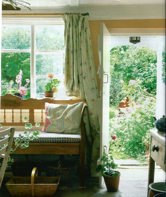 a stylish vintage rustic sunroom with wooden furniture, floral and other print textiles, potted blooms and greenery