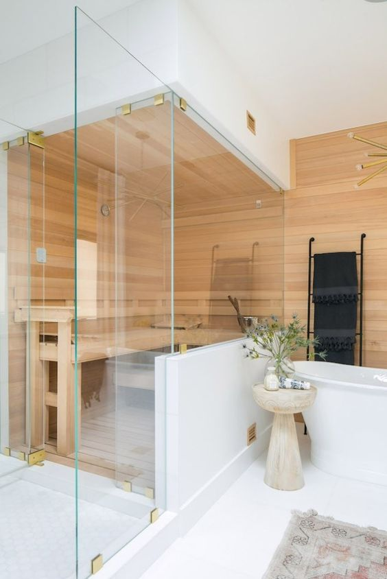 a tiny built-in steam room clad with wood and with a large bench is very cozy and relaxing