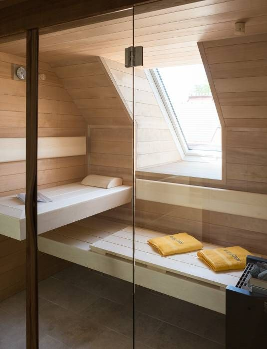 a tiny home steam room clad with light stained wood and a couple of benches plus a small window for natural light