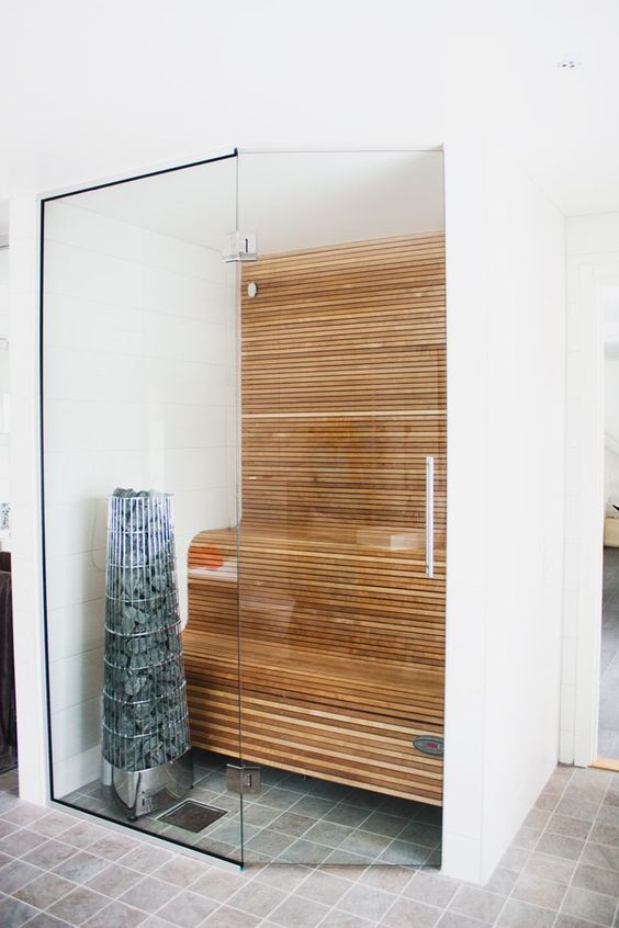 a tiny minimalist steam room clad with wood and with curved benches plus glass walls is cool