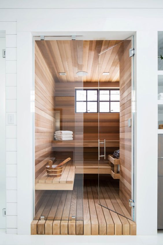 a tiny steam room with windows, a couple of long benches and some additional accessories is chic