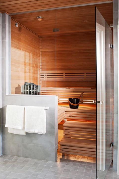 a tiny welcoming steam room clad with wood, with step benches and lights built-in under the steps