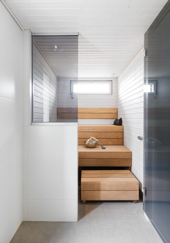 a tiny yet chic steam room clad with light stained and white wood, with step benches and a small skylight