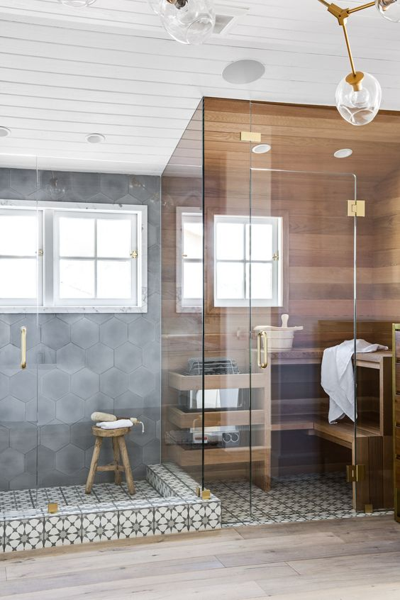 a tiny yet chic steam room covered with wood, with two benches and a window plus touches of gold