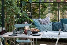 a vintage Nordic sunroom with some folding furniture and a large daybed, blue printed textiles and potted greenery