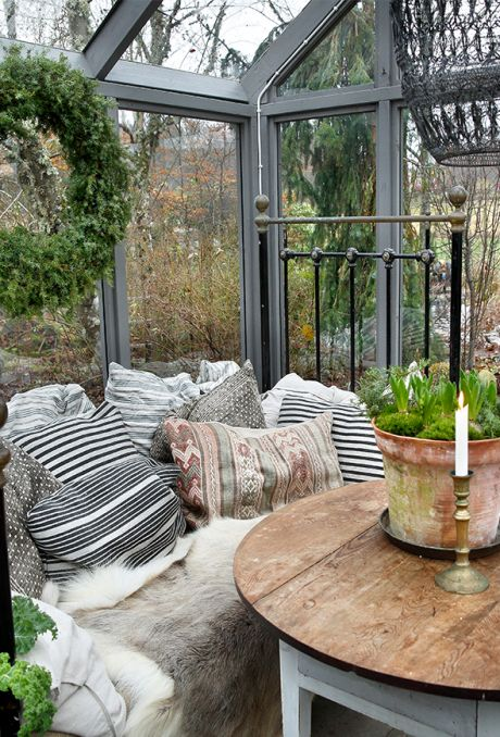 a vintage Scandinavian sunroom with wooden furniture, printed pillows, faux fur, greenery and candles
