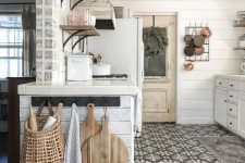 a vintage cottage kitchen in neutrals, with planked cabinets, stained shelves, a mosaic tile floor, metal pendant lamps and pans