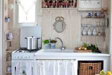 a vintage cottage kitchen with a checked floor, neutral stained walls, open and usual cabinets, baskets and fun textiles
