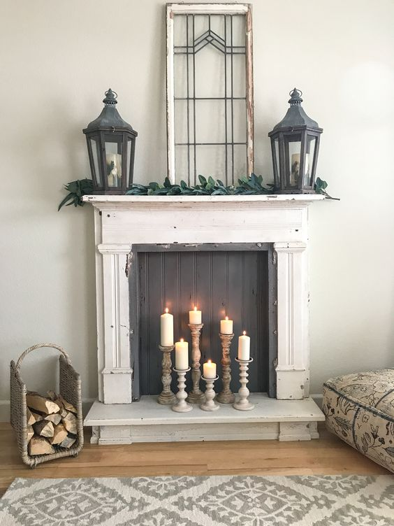 a vintage fireplace with a black screen and candles in wooden candle holders