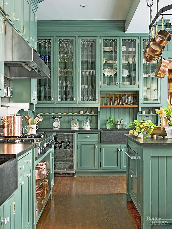 a vintage green kitchen with a beadboard backsplash, dark counertops, copper cookware and pans for decor is a bold and unusual idea