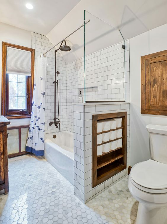 a vintage-inspired bathroom with white and marble tiles, with a half wall that has soem integrated storage space, touches of stained wood for more coziness