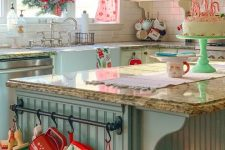 a vintage kitchen styled for Christmas, with neutral and blue cabinets, grey stone countertops, open shelves, a wreath and some other winter decor