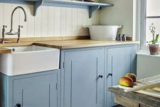 a vintage kitchen with blue cabinetry and shelves, a rough wooden table, a beadboard backsplash, a printed rug and butcherblock countertops