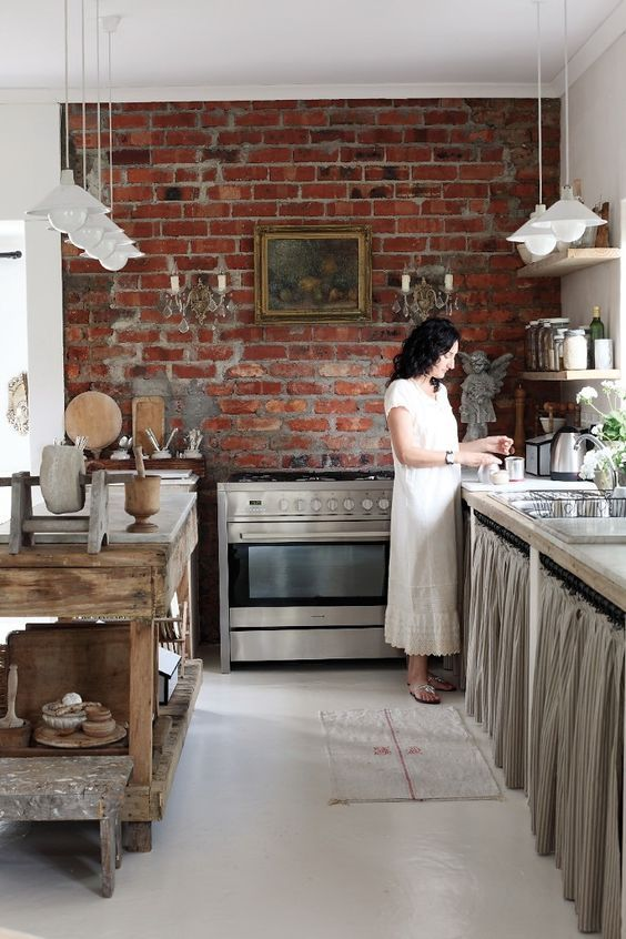 a vintage kitchen with industrial touches, simpel cabinetry with curtains, a wooden kitchen island, pendant lamps and a exposed red brick wall