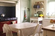 a vintage kitchen with neutral cabinets, a burgundy cooker and a navy subway tile backsplash, a neutral vintage dining set and touches of green