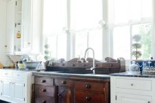 a vintage kitchen with white cabinets, a dark stained vanity of a vintage dresser, pendant lamps, printed rugs and lots of windows
