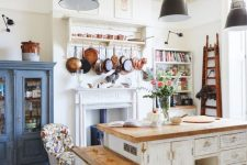 a vintage kitchen with white shabby chic cabinets, butcherblock countertops, black pendant lamps, a blue buffet and a vintage hearth