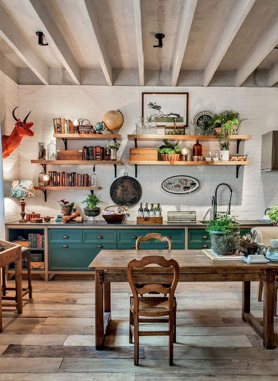 a vintage rustic kitchen with teal and stained cabinets, a stained dining set with vintage chairs, open shelves and an orange faux taxidermy piece