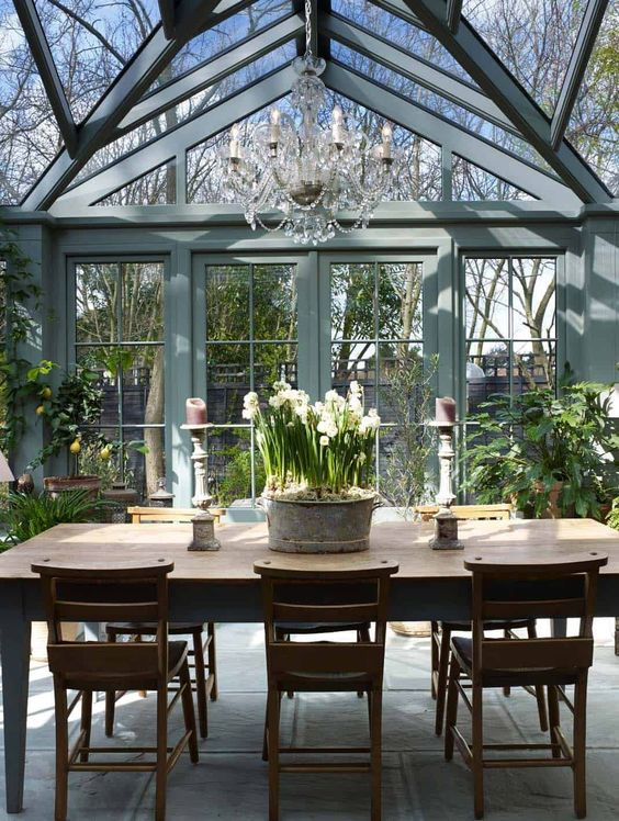 a vintage rustic sunroom in blue grey, with stained rustic furniture, potted greenery and blooms and a crystal chandelier