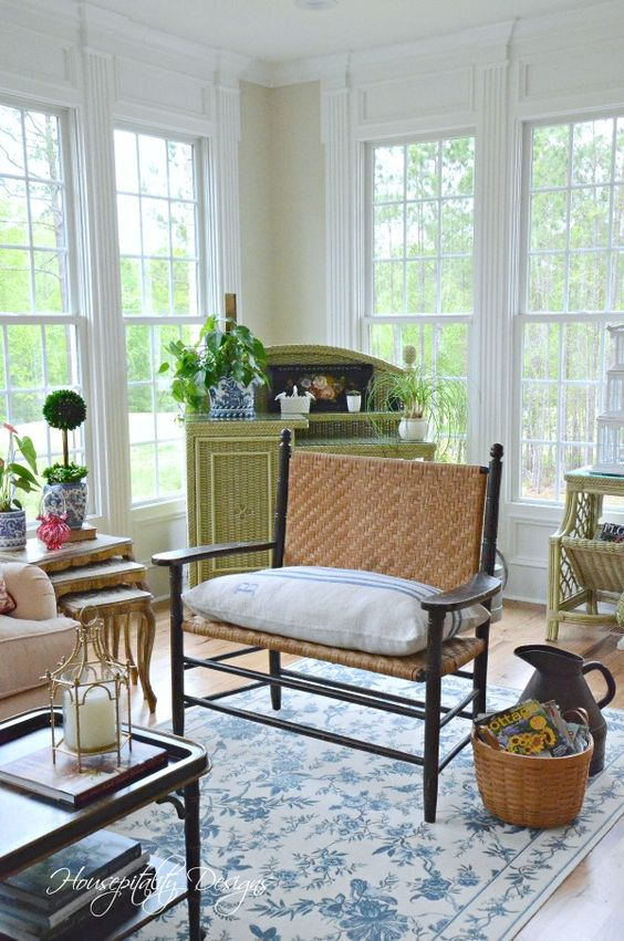 a vintage rustic sunroom with green and neutral wicker furniture, neutral textiles, potted greenery and a floral rug