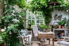 a vintage rustic sunroom with wooden furniture, printed textiles, potted greenery and blooms and lots of greenery