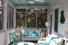 a vintage sunroom with white and turquoise furniture, potted textiles and a working nook with a desk