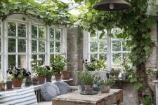 a vintage to shabby chic sunroom with neutral and stained furniture, potted greenery and blooms and vining greenery on the ceiling