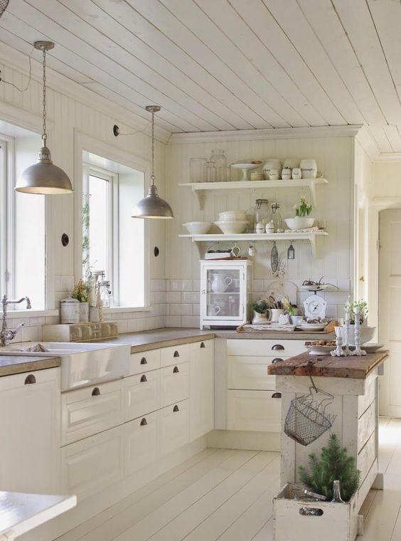 a vintage white Scandinavian kitchen with a small kitchen island, butcherblock coutnertops, a white subway tile backsplash, open shelves and pendant lamps