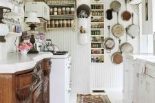 a vintage white kitchen with a stained buffet as cabinetry, white cabinets, white beadboard walls, open shelves and vintage pans for decor