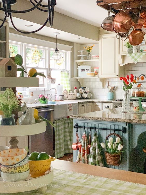 a vitnage cottage kitchen with white cabinets, a blue kitchen island, printed textiles, bright blooms and greenery and copper cookware