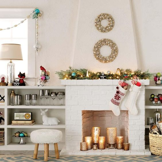a white brick fireplace with gold mercury glass candle holders with pillar candles