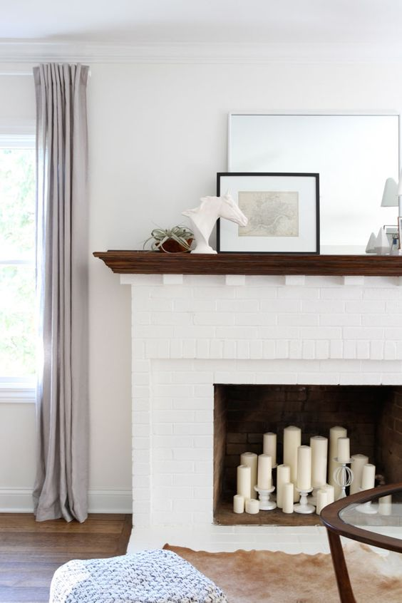 a white fireplace with a dark stained mantel and white pillar candles in the fireplace and on candle holders