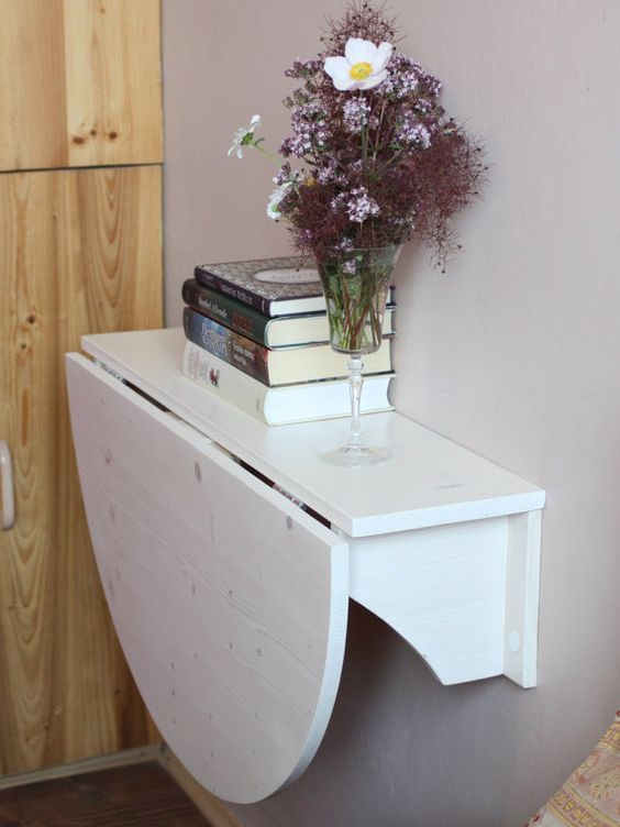 a white foldable wall-mounted desk or breakfast table is a great way to save some space