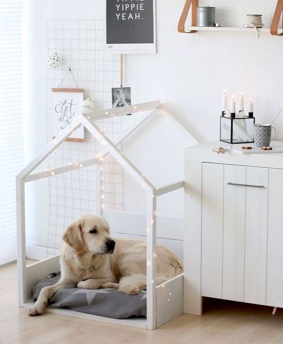 a white house-shaped dog bed with lights and a star-printed cushion is a pretty idea for a Scandinavian interior