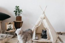 a white teepee with pompoms is a creative and fun cat bed and house in one, perfect for a boho interior
