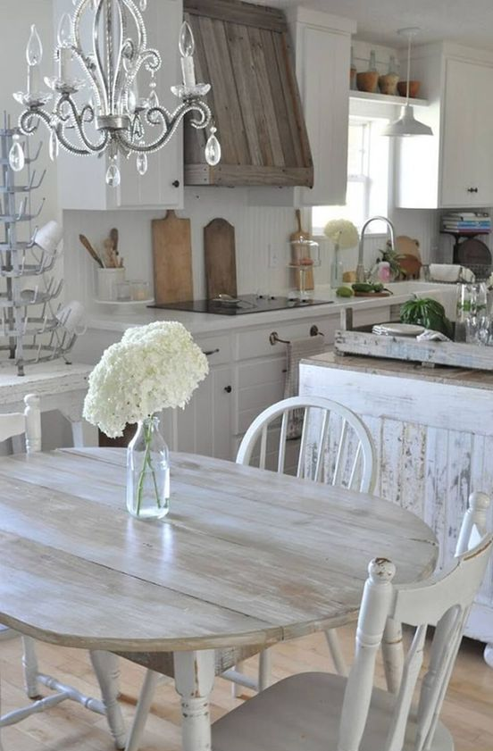 a white vintage kitchen with a shabby chic kitchen island, a wooden hood, pendant lamps and a crystal chandelier, a shabby chic dining set