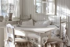 a white vintage sunroom with forged and wooden furniture, floral textiles, a metal lamp and a large mirror