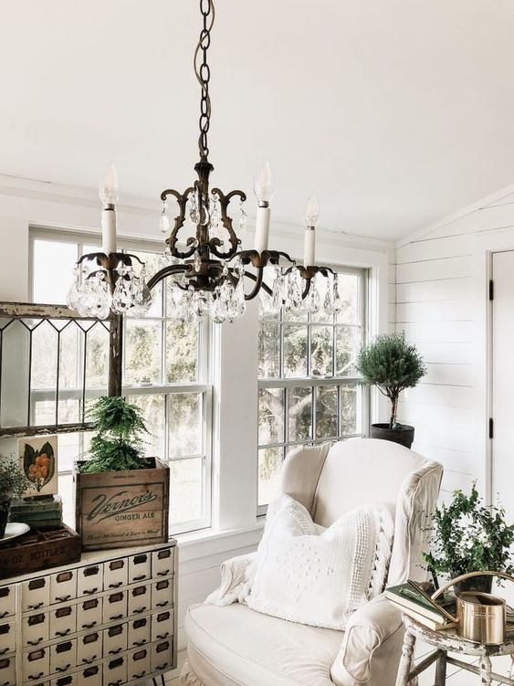 a white vintage sunroom with neutral furniture, a vintage storage unit, a crystal chandelider and potted greenery
