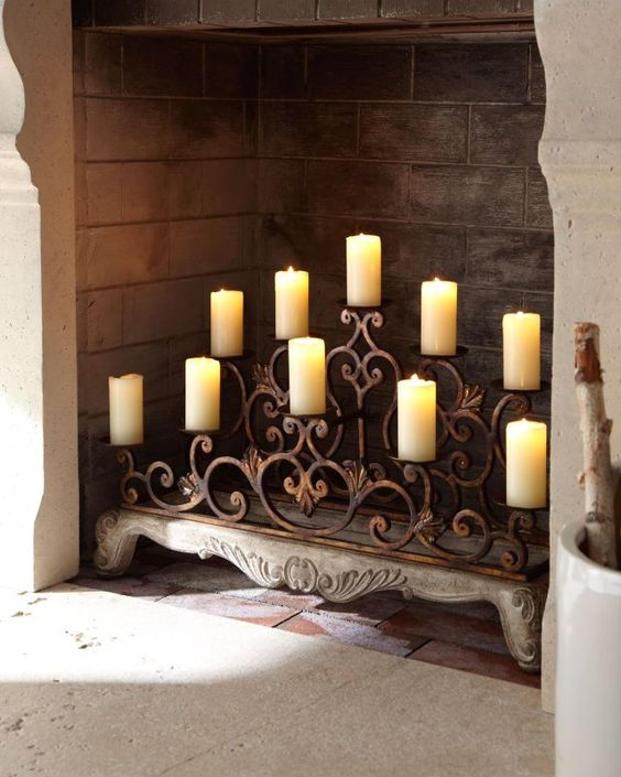 a wrought candle stand with vignettes right in the fireplace is a refined idea to try