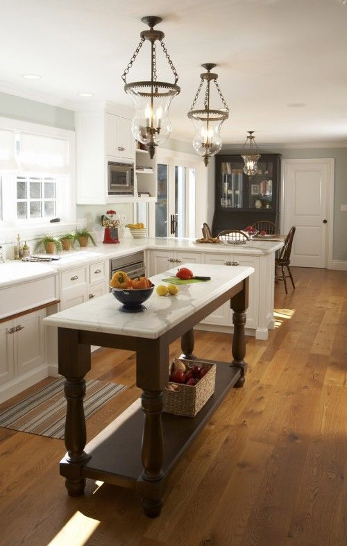 an elegant vintage kitchen with shaker style cabinets, a dark stained kitchen island, vintage chandeliers and potted herbs