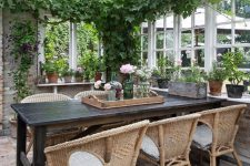 an enchanting vintage sunroom with a black table, wicker chairs, potted greenery and blooms and suspended lamps