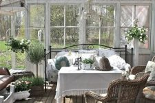 an exquisite vintage rustic sunroom with a forged daybed, wicker chairs, potted greenery and blooms and a vintage chandelier