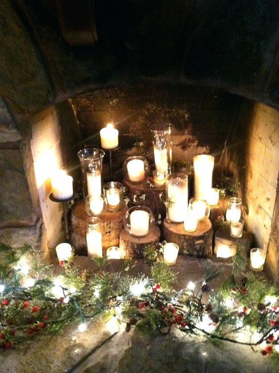 tree stumps with candles in glass candle holders and some greenery and pinecones around